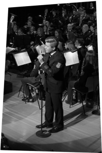 Sänger und Hornist Sebastian Römer am Mikrophon vor dem Orchester.