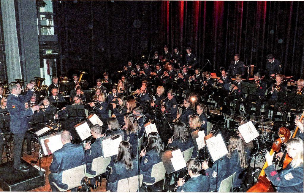 Foto des Orchesters. Andreas Reuber beim Dirigat, die Musikerinnen und Musiker im Spiel.