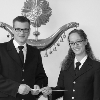 Sören Wehn (links) übergibt den Taktstock an die neue Dirigentin der Jungen Harmonie Emi Bosch (rechts).